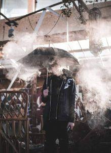 Was will ich wirklich - Mann unter Regenschirm Rauch