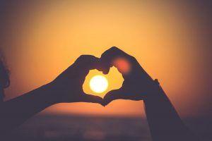 Streit vermeiden - Zwei Hände formen ein Herz vor dem Sonnenuntergang