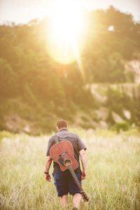 Beziehungsprobleme lösen - Mann mit Gitarre läuft in den Sonnenaufgang