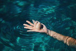 Kompromisse eingehen - Muschel in Handfläche im Wasser