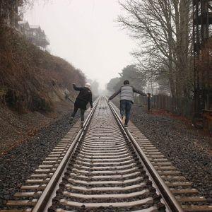 Beziehungsprobleme lösen - Mann und Frau balancieren auf Bahngleisen