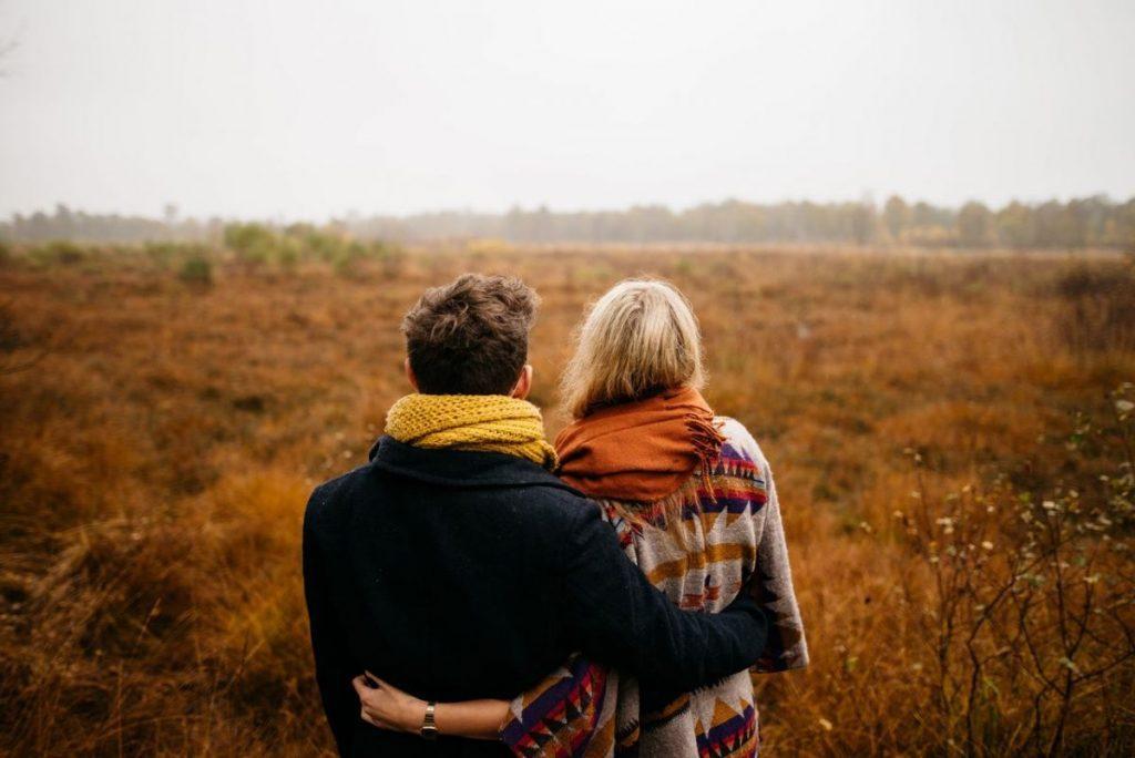 Beziehungsprobleme lösen - Paar schaut Arm in Arm in die Ferne