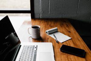 Was will ich wirklich - Schreibtisch mit Laptop, Kaffee und Schreibblock
