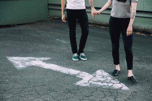 Was will ich wirklich - Pärchen steht auf Straße mit Straßenmarkierung in unterschiedlichen RIchtungen