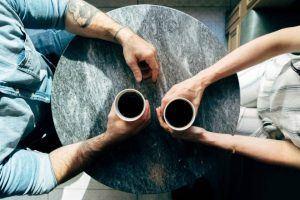 Streit vermeiden - Mann und Frau sitzen gegenüber am Tisch mit Kaffeetassen