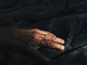 Lebensziele finden - Hand eines alten Mannes auf Bettdecke