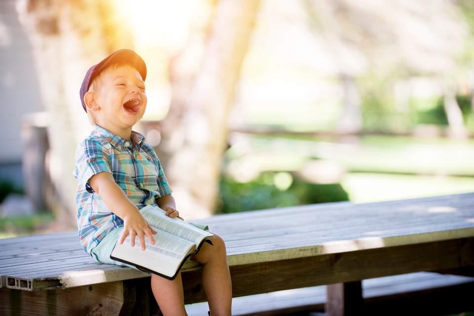 Lebensfreude wiederfinden - Junge sitzt auf einer Bank und lacht