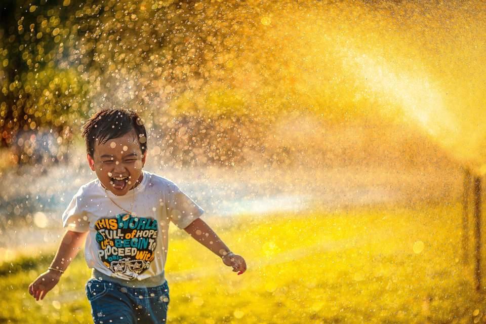 Lebensziele finden - Lachendes Kind rennt durch Wassernsprenkler