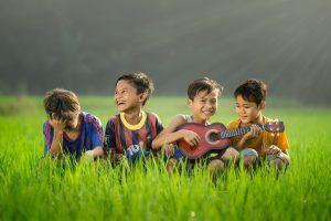Lebensfreude wiederfinden - 4 Jungen sitzen im Gras, lachen
