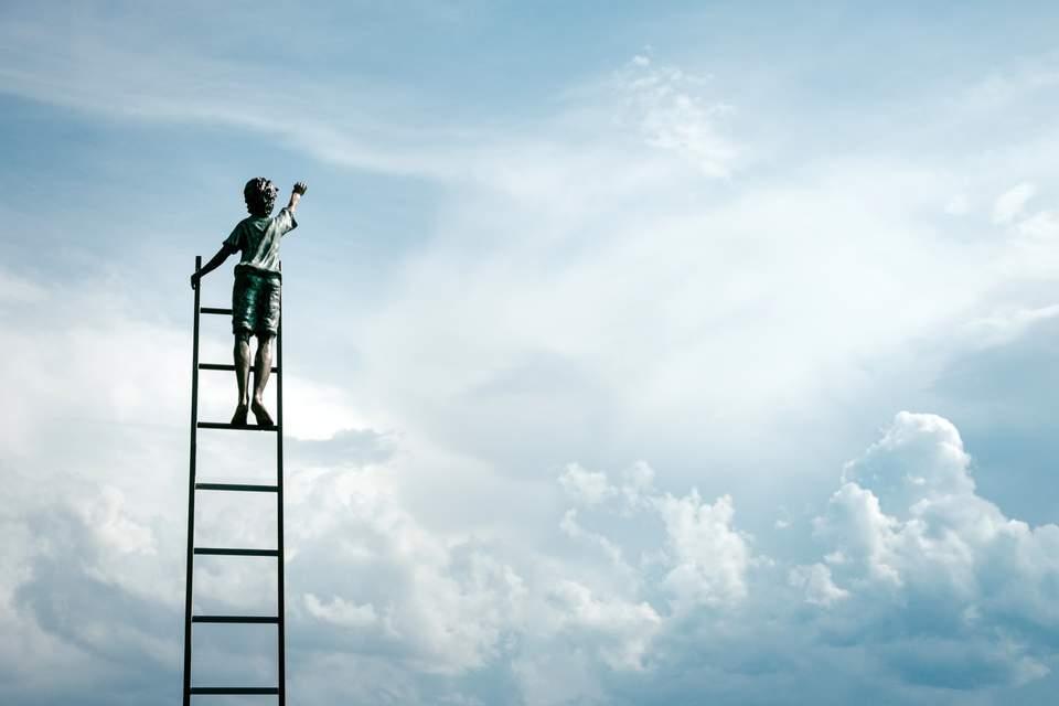 Persönliche Werte finden - Mensch auf Leiter vor blauem Himmel