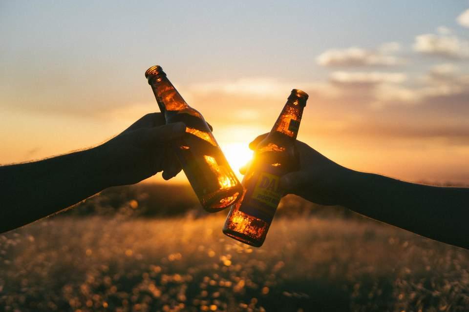 Antriebslosigkeit überwinden - Zwei Männer stoßen mit Bierflaschen vor SOnnenuntergang an
