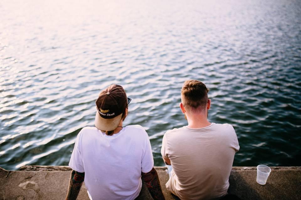 Kein Bock auf Arbeit - Zwei Männer sitzen am Wasser und sprechen