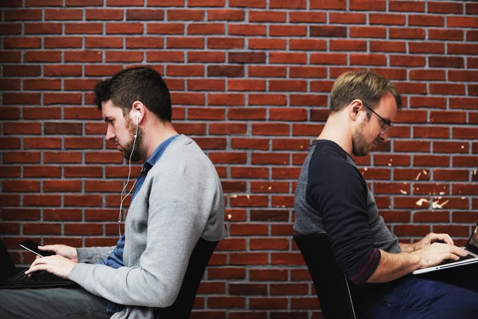 Kein Bock auf Arbeit - Zwei Männer Rücken an Rücken schauen in ihren Laptop