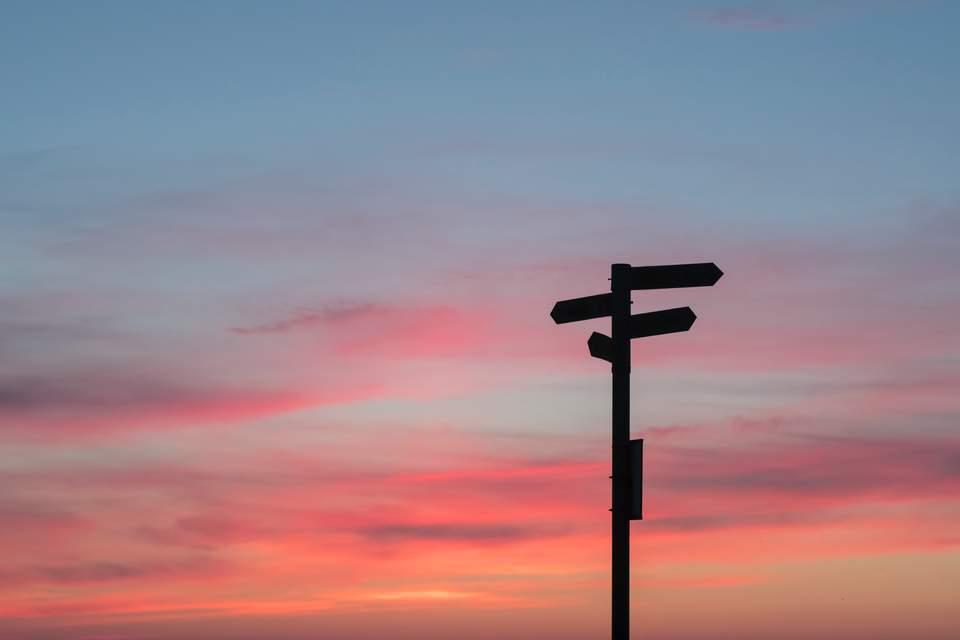 Selbstfindungsphase - Wegweiser vor rotem Horizont