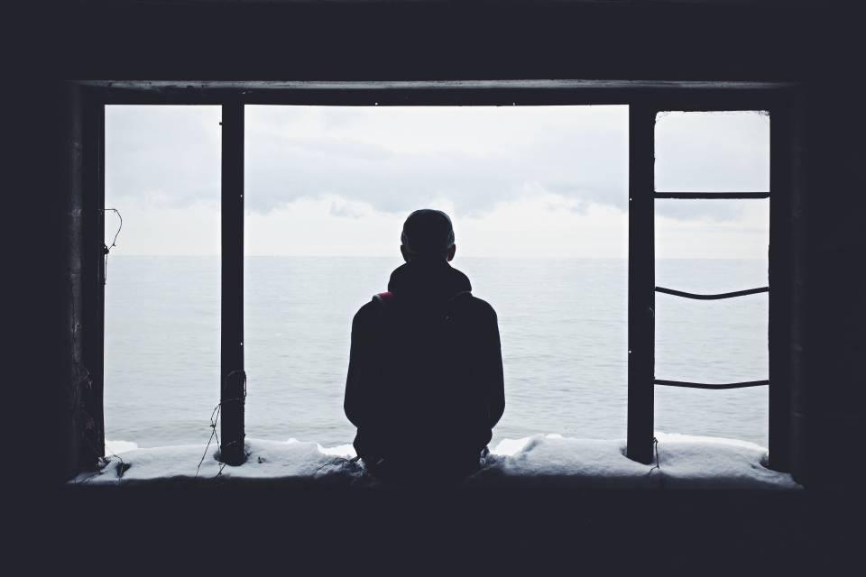 Selbstfindungsphase - Mann sitze am Fenster und schaut aufs Meer